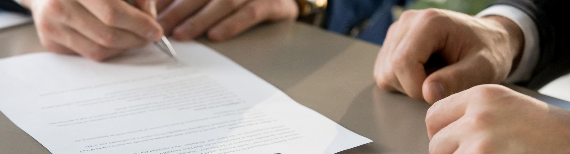 Mains d'hommes d'affaires rédigeant un contrat