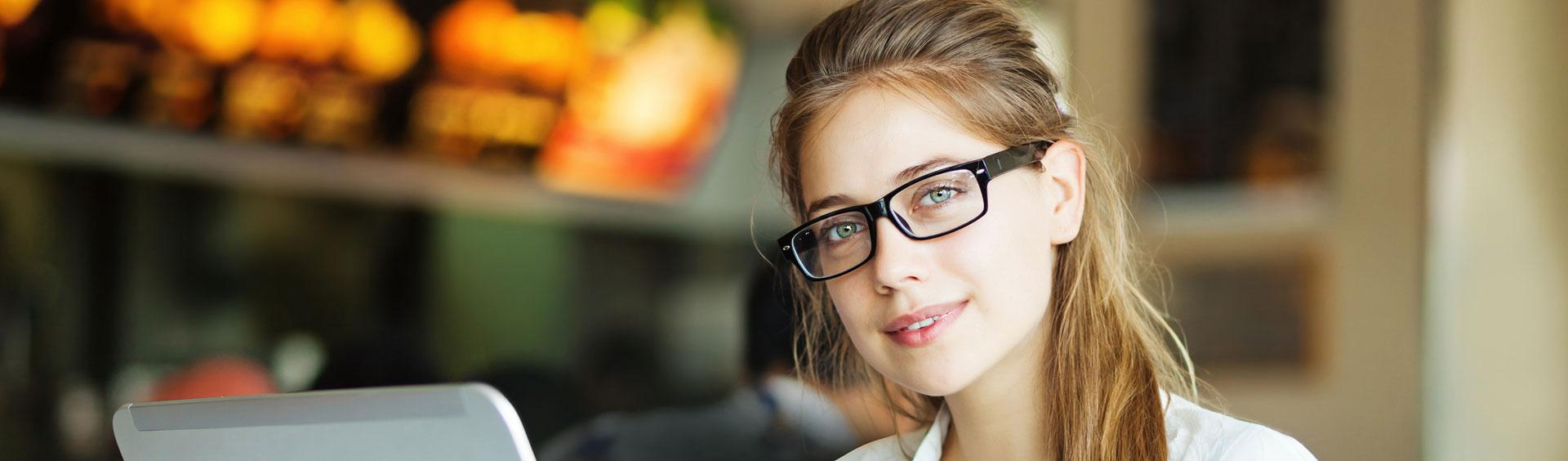Jeune fille portant des lunettes derrière son ordinateur